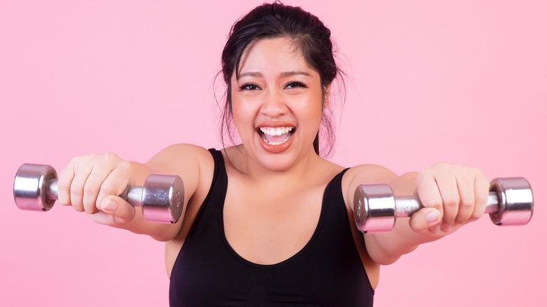 femme souriante et soulevant des poids libres