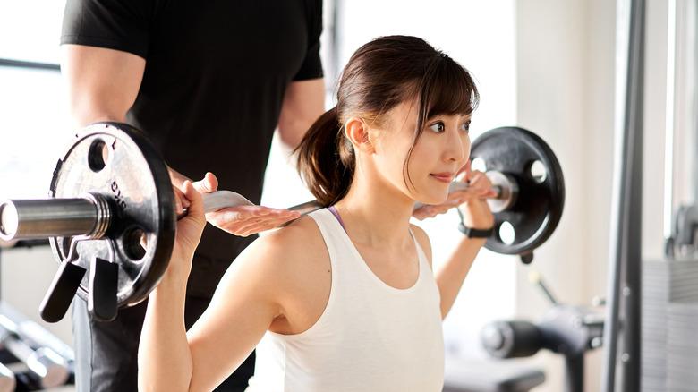 femme soulevant des poids avec spotter