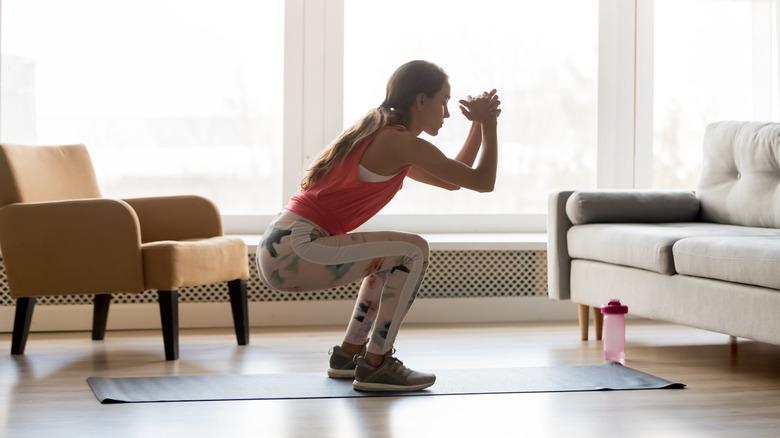 Une femme fait des squats à la maison