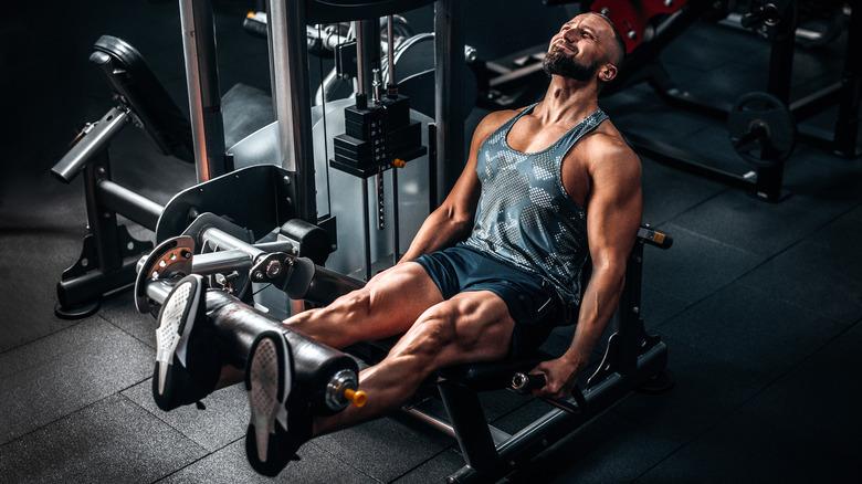 homme musclé sur machine à jambe dans la salle de sport
