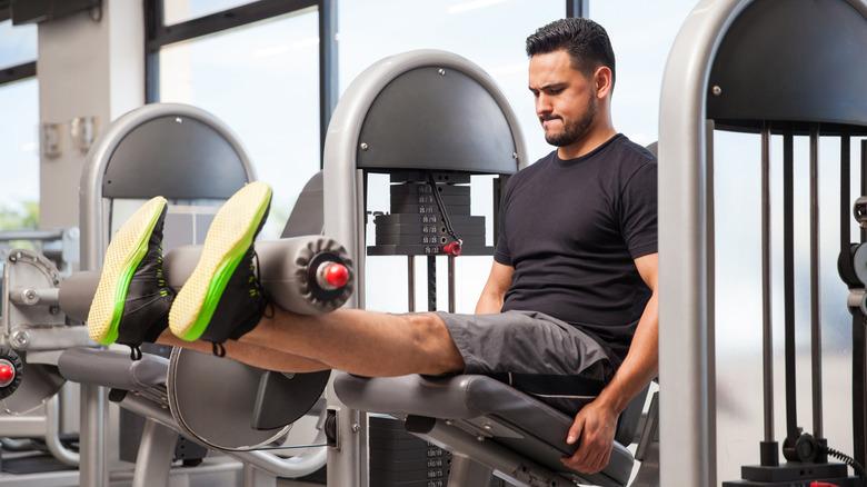 Un homme utilise une machine d'extension de jambe
